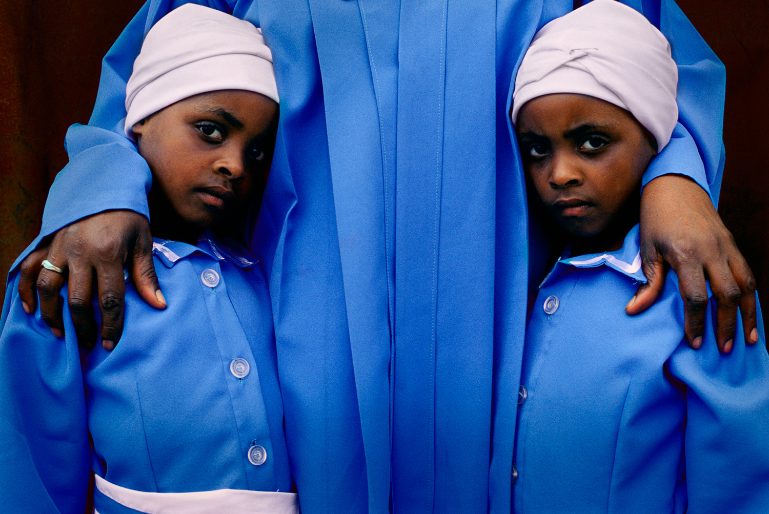 Twin girls attend an early morning church service at a Zion church in Site B Khayelitsha, South Africa, July 2001.