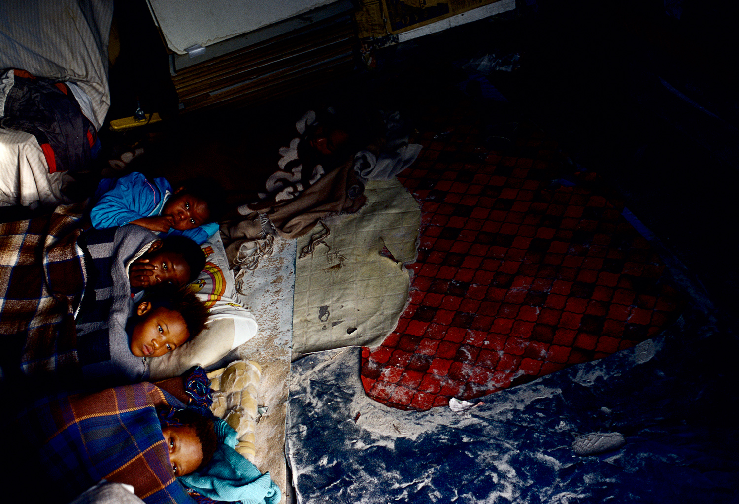 Children wake in their one-roomed shack in Site B, Khayelitsha, South Africa, August 2001.