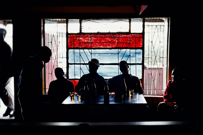 Men drink in an illegal bar (shebeen) in Site C, Khayelitsha, South Africa, June 2002.