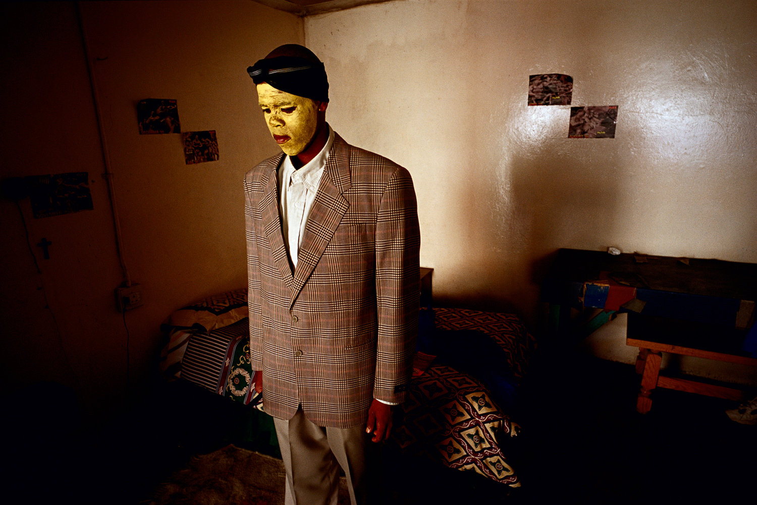 Luxolo Mkwelo, age 19, stands in his room after coming home from a traditional manhood ceremony in Tshatshu, South Africa, August 2000. He spent six weeks in the bush learning to be a man. He was circumcised and elders guided him during the ceremony, which is to prepare them for adulthood. Former South African president Nelson Mandela went trough the ceremony when he was young.