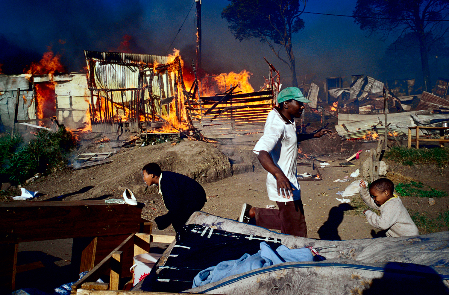 Residents rush to save their belongings as a shack fire is raging in Duncan Village, a poor township outside East London in Eastern Cape province, South Africa, November 2005. It's on of the poorest areas in South Africa. Fires are very common as the shacks are built very close to each other and people are using paraffin stoves, which easily fall over, and the fires spread quickly.