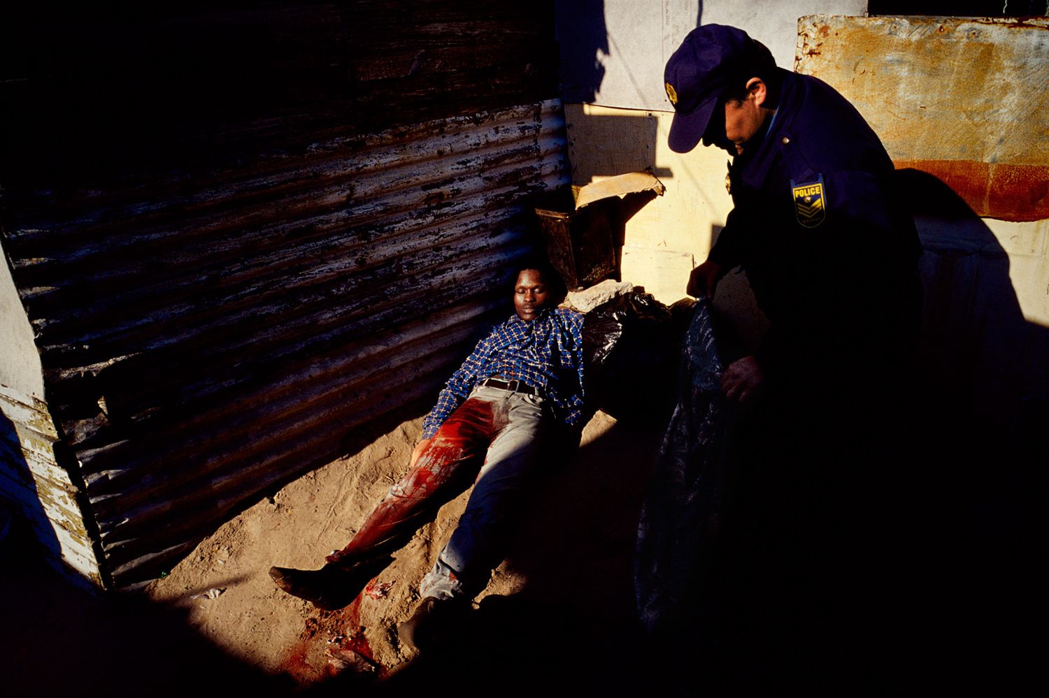 A policeman places a blanket over a man killed by gunfire in Khayelitsha, the largest black township outside Cape Town, South Africa, January 2008.