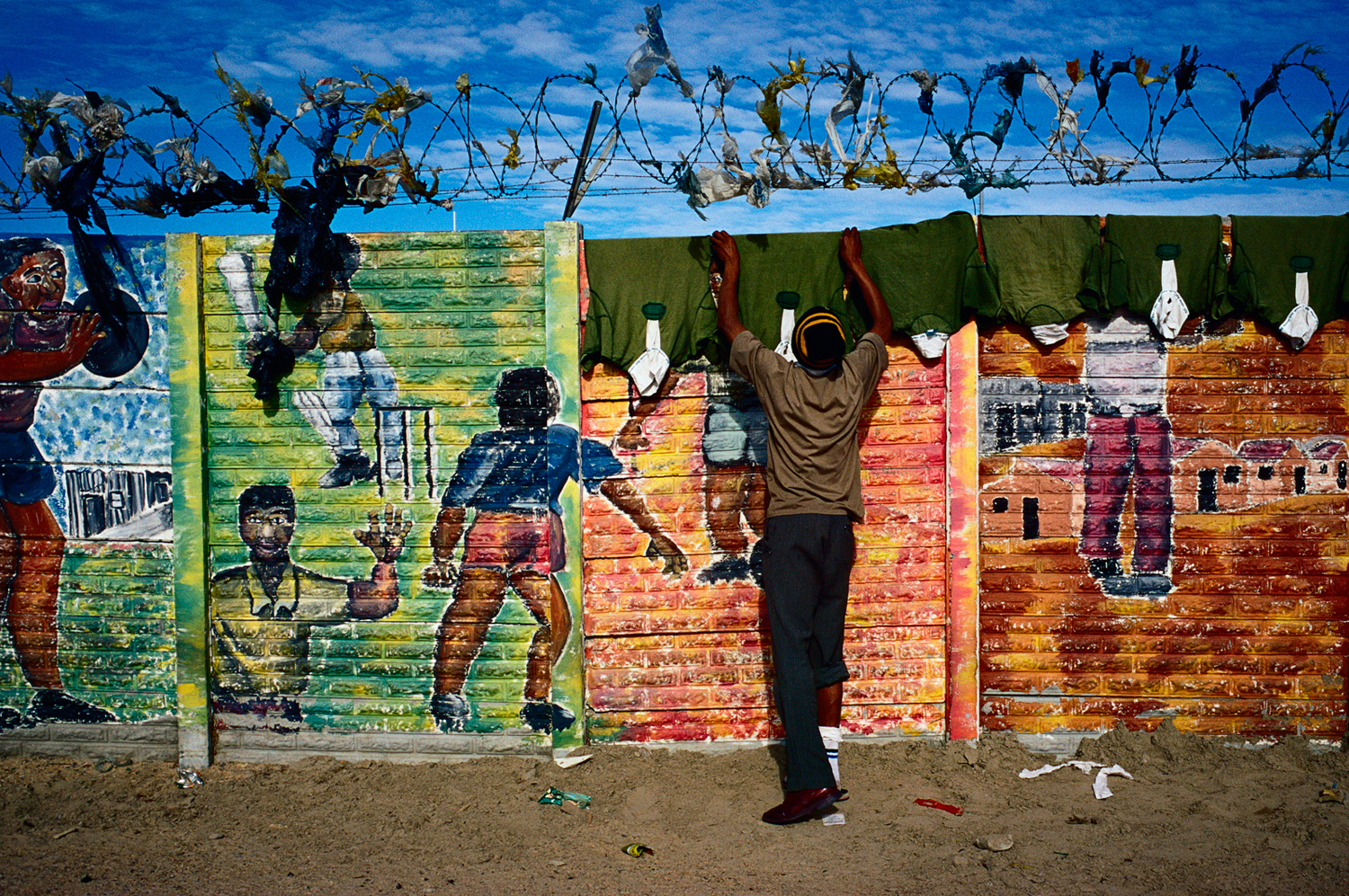 A man hangs rugby shirts that have been laundered on a colorful wall with graffiti in Site C Khayelitsha, a township about 35 kilometers outside Cape Town, South Africa, July 2001.