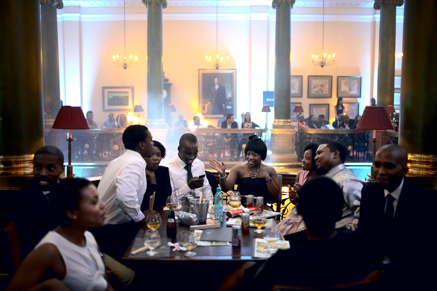 Wealthy black South Africans wait for a fashion show at the Rand Club in Johannesburg, South Africa, February 2011. The Rand Club, A former private all male club during the Apartheid era. Here, the wealthy industrialists of the country networked, wined and dined. The club now allows female members. To see newly wealthy black people in the club is a sign on the new South Africa.