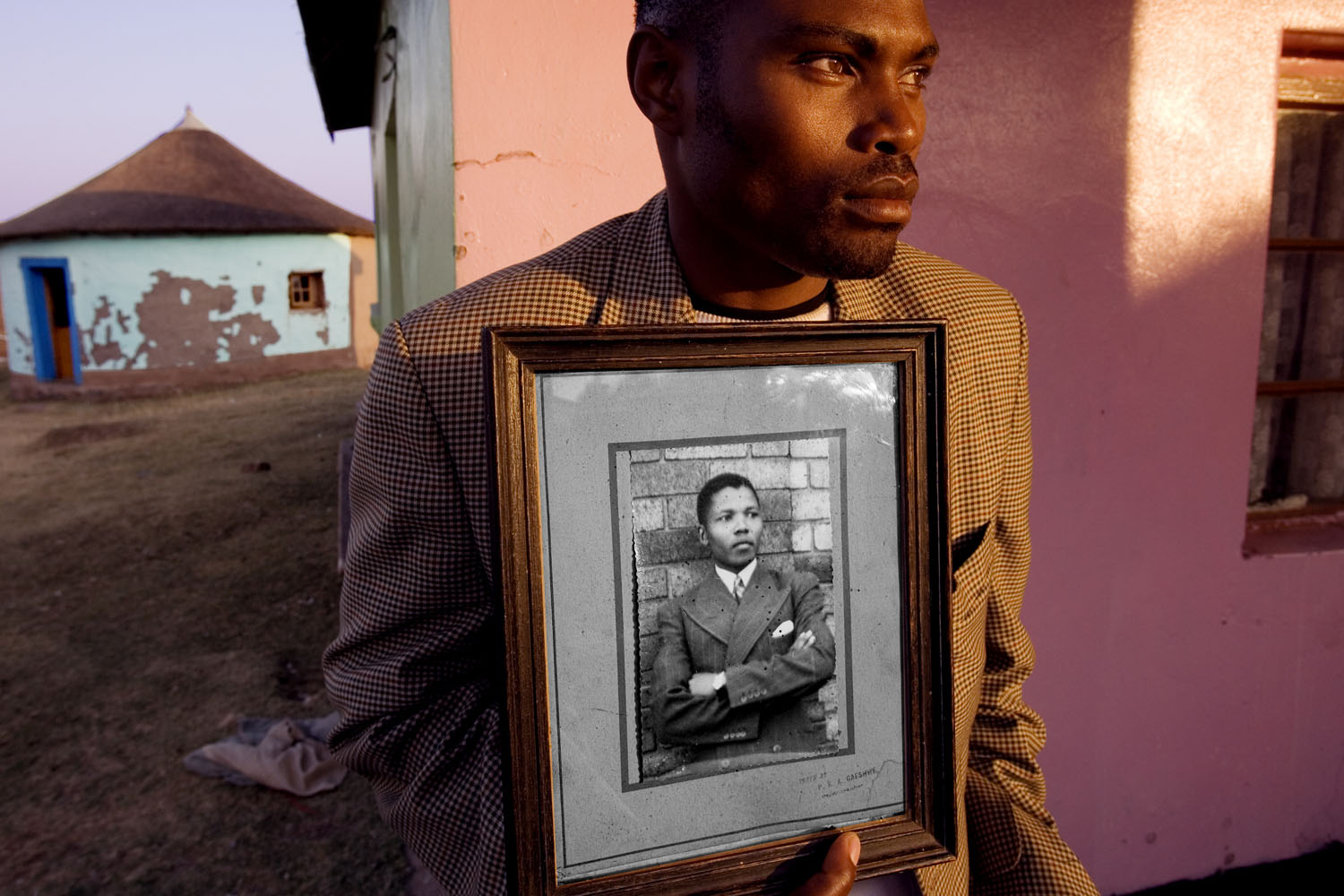 'Madiba' Nelson Rolihlahla Mandela was raised in the rural Transkei, born into the Xhosa Thembu Royal family. At age 22, after studying at the prestigious Fort Hare University when the portrait in this photograph was made, 'Madiba' returned to the village to find that his Chieftan father had arranged marriages for him and his adopted brother, Justin. It was at this moment that Mandela, resisting, took a train to Johannesburg and was quickly catapulted into a leadership role to end apartheid. The young man in this photograph, holding the portrait of 'Madiba' in college, is a distant relative who lives in the village of Mqhekezweni, in the Transkei, where this original portrait still sits on the mantel of the family home.