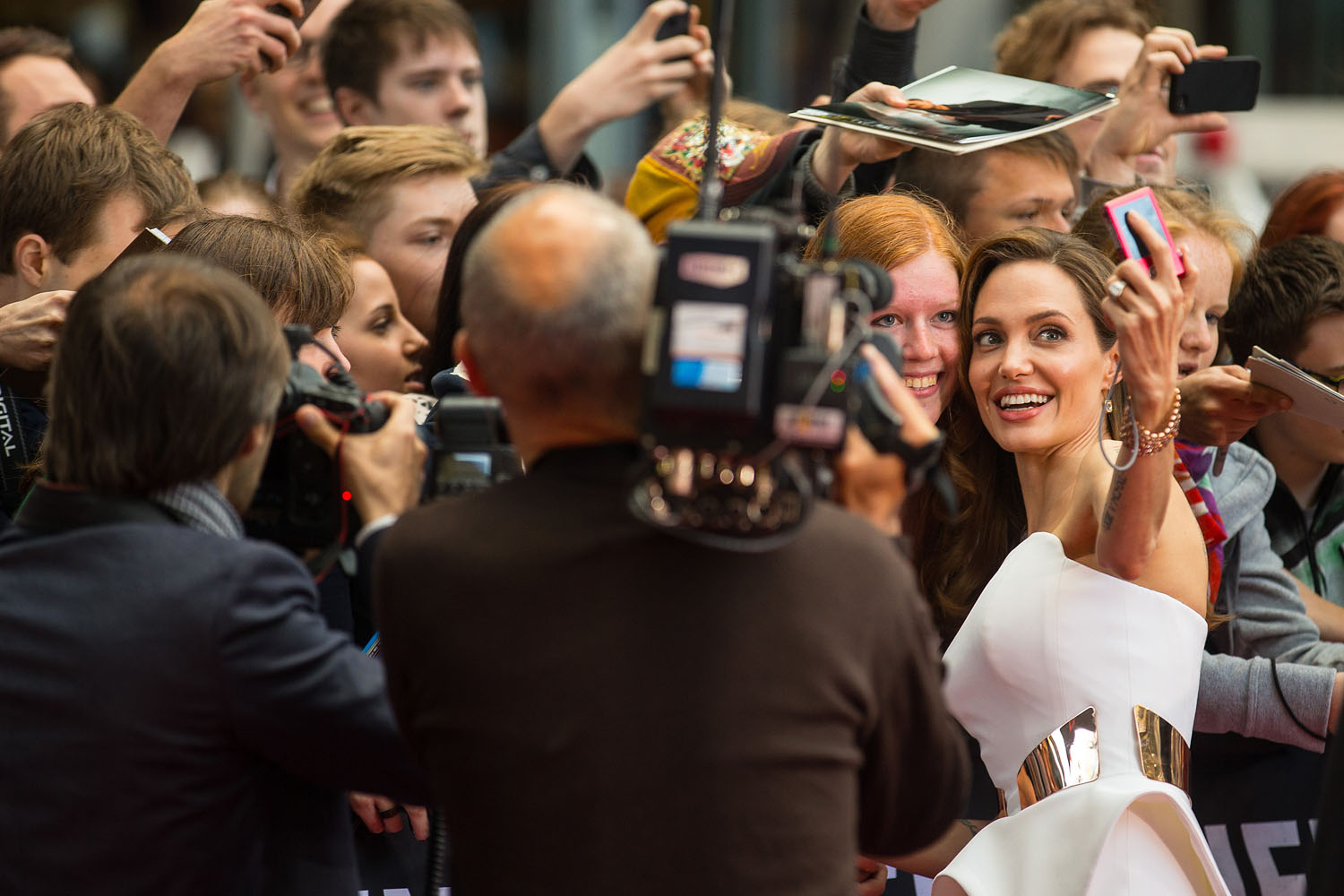 June 4, 2013. US actress Angelina Jolie poses for photos with fans as she arrives for the German premiere of the film  World War Z  at the Cinestar movie theater in Berlin.
