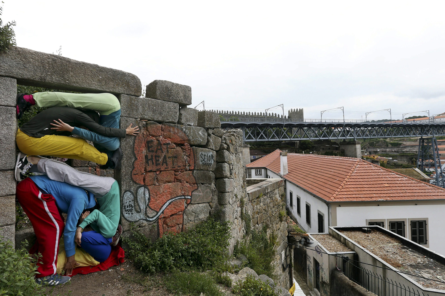 June 6, 2013.  Performers squeeze their bodies into selected spots of architectural structures as part of the 'Bodies in Urban Spaces' project in Porto, Portugal.