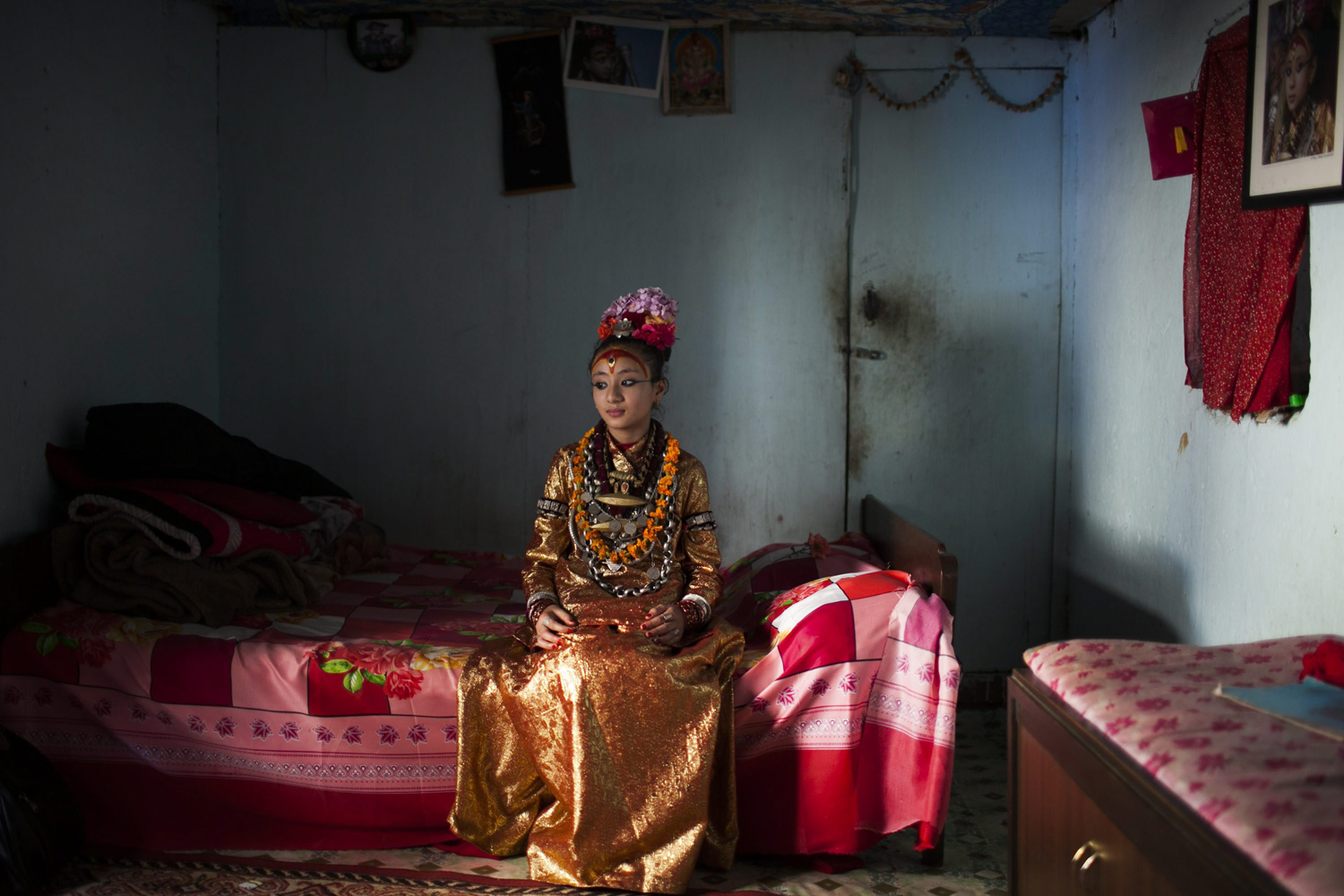 June 7, 2013. Kumari Samita Bajracharya, aged 10, waits for the procession to attend the Rato Machindranath chariot festival, also known as Bhoto Jatra, in Jwalakhel, on the outskirts of Kathmandu.