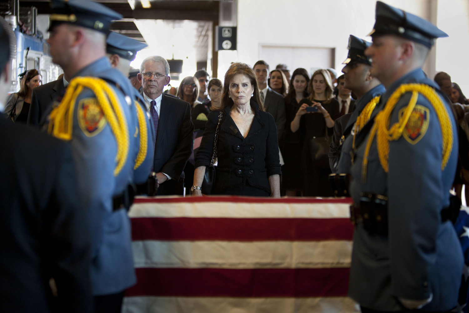 June 5, 2013. Senator Frank Lautenberg's widow Bonnie Englebardt Lautenberg (C) looks on as his casket is wheeled onto a train bound for Washington, following a color guard ceremony and final New Jersey send-off for him at the train station that bears his name, in Secaucus, New Jersey.