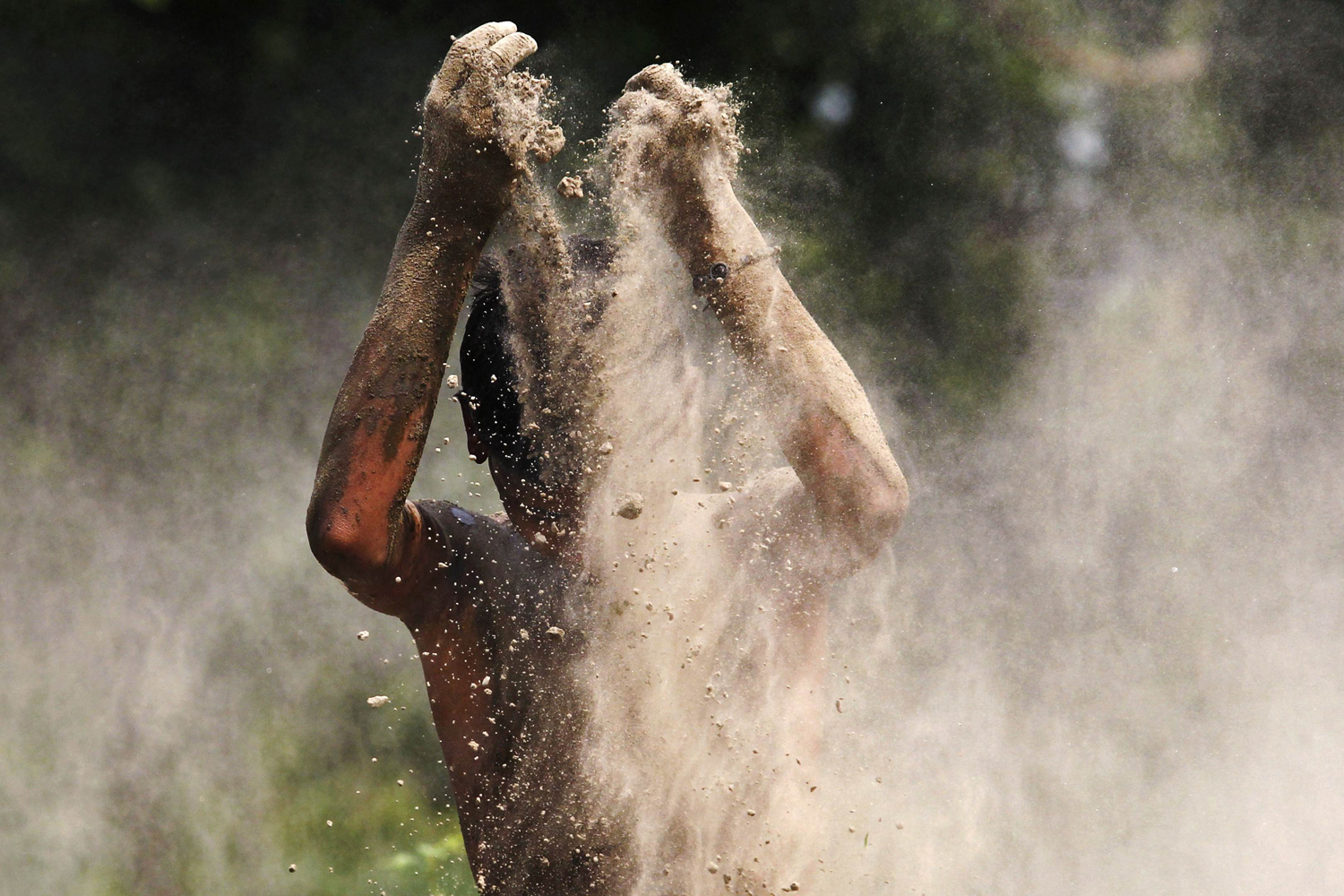 June 7, 2013. A boy plays with mud on the banks of river Yamuna on a hot day in New Delhi.