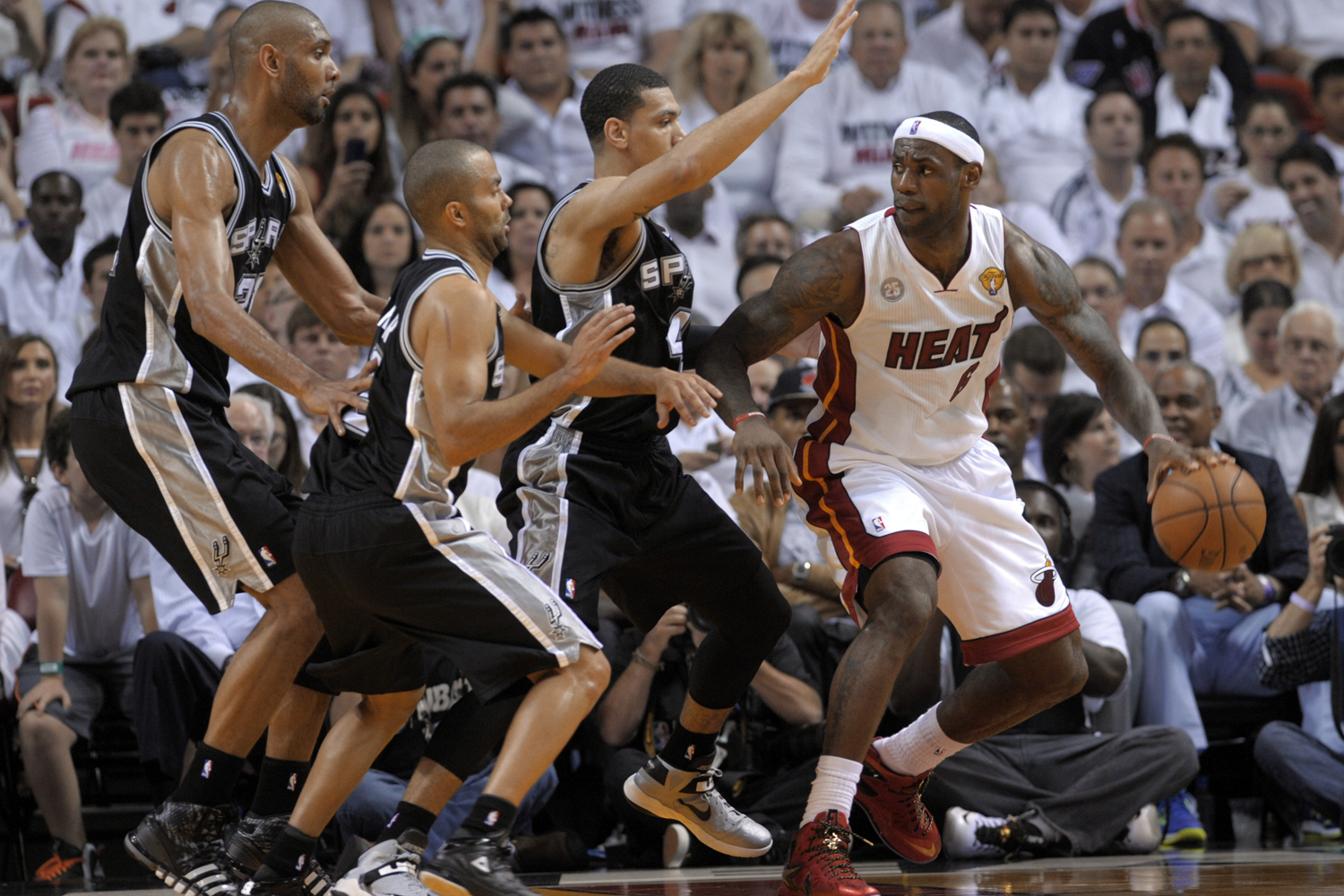 June 6, 2013. LeBron James (R) of the Miami Heat tries to navigate before the trio of Danny Green (3rd-L), Tony Parker (2nd-L) and Tim Duncan (L) of the San Antonio Spurs in the first half during Game One of the NBA Finals at American Airlines Arena in Miami, Florida.