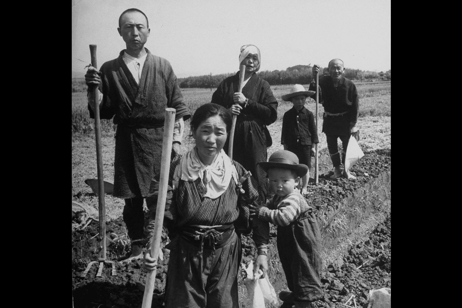 A postwar Japanese farming family posing with their tools in the field, 1948.