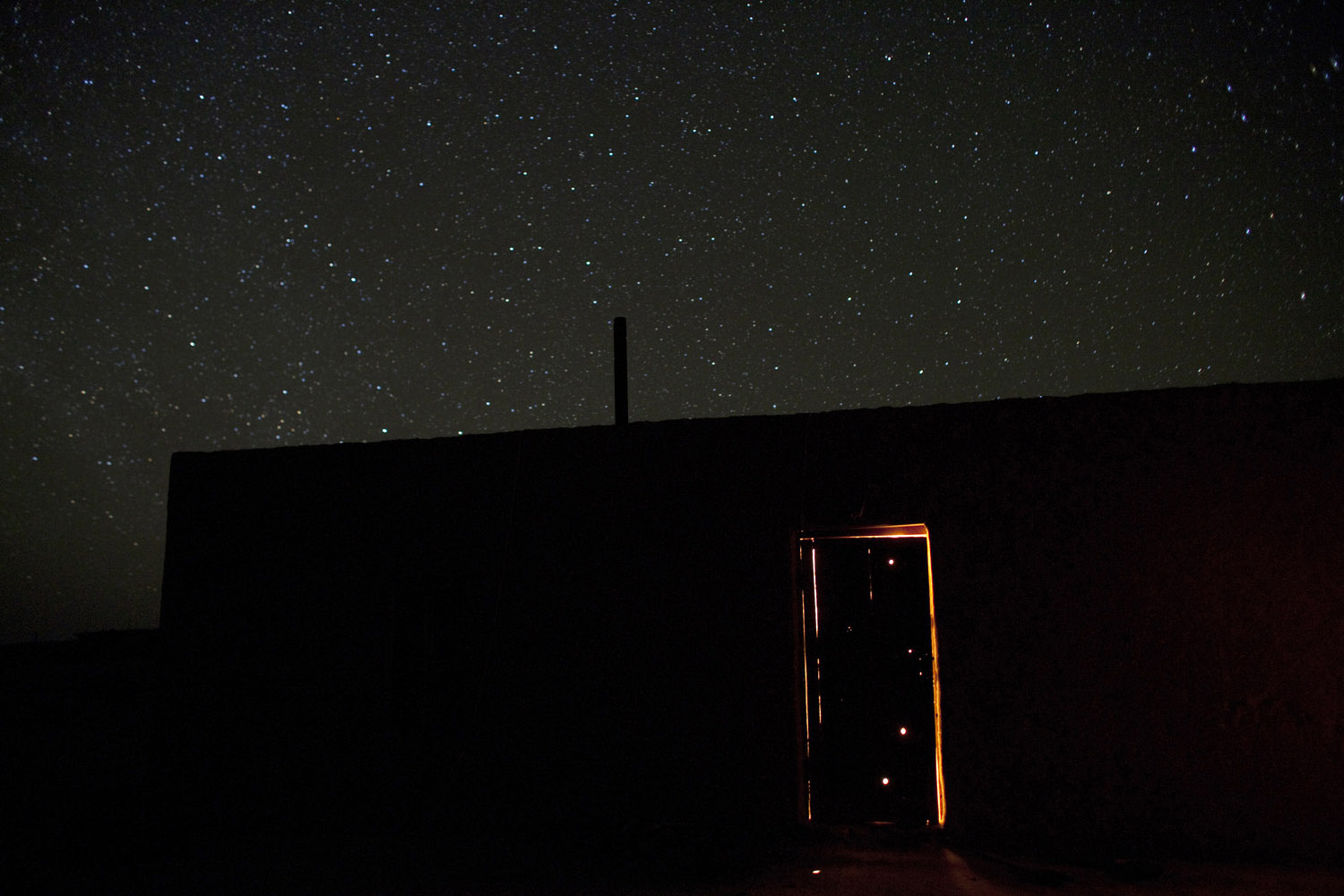 Bullet holes and stars are lit at night in Damla, a desert village whose name means  Drop of Water.                                Damla, Turkmenistan