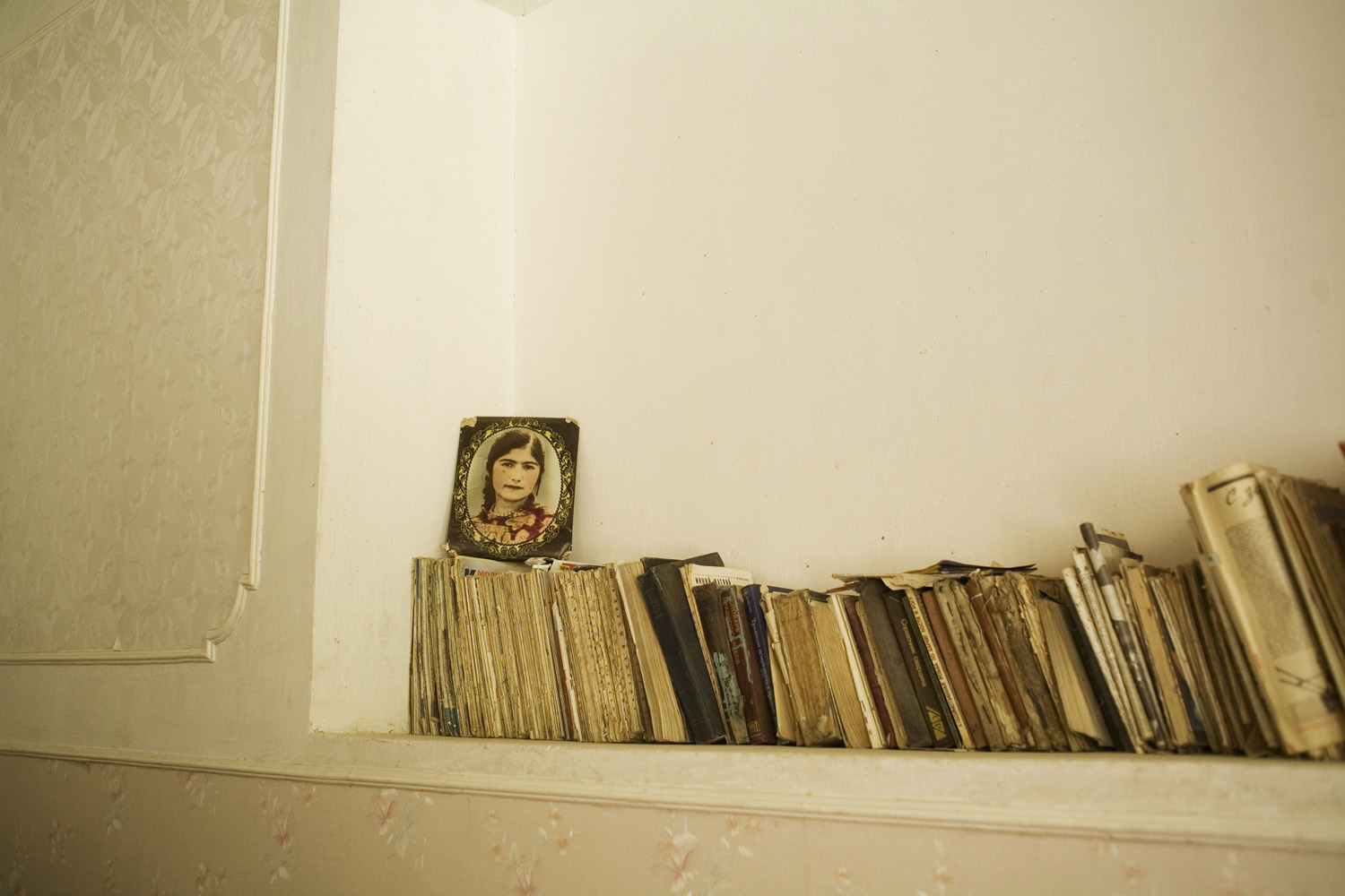 A shelf of books and a framed picture displayed in a Pamiri home, high and isolated in the Tajik Pamir mountains.                               Bartan, Tajikistan