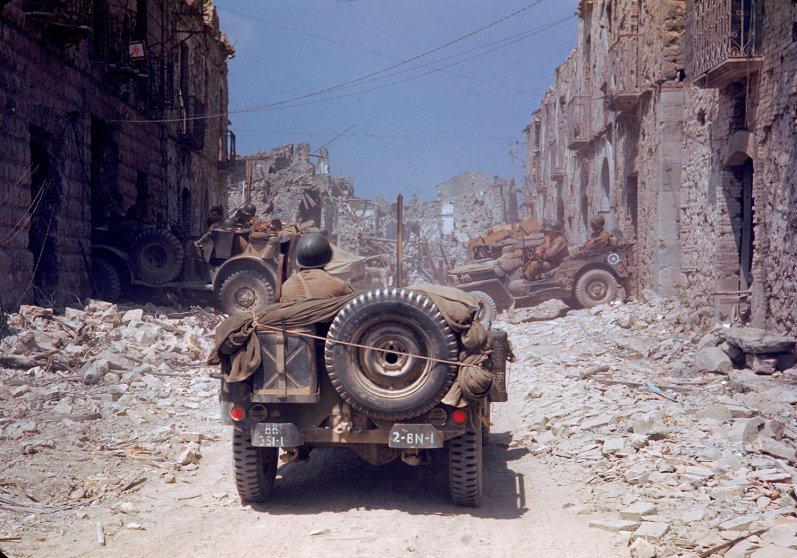 American jeeps travel through a bombed-out town during the drive towards Rome, World War II.