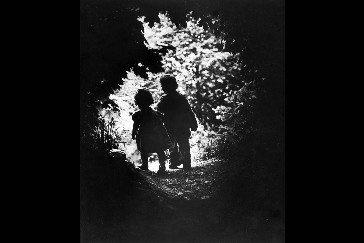Children of photographer W. Eugene Smith walking hand-in-hand in the woods behind his home in this photograph entitled  The Walk to Paradise Garden,  1946.