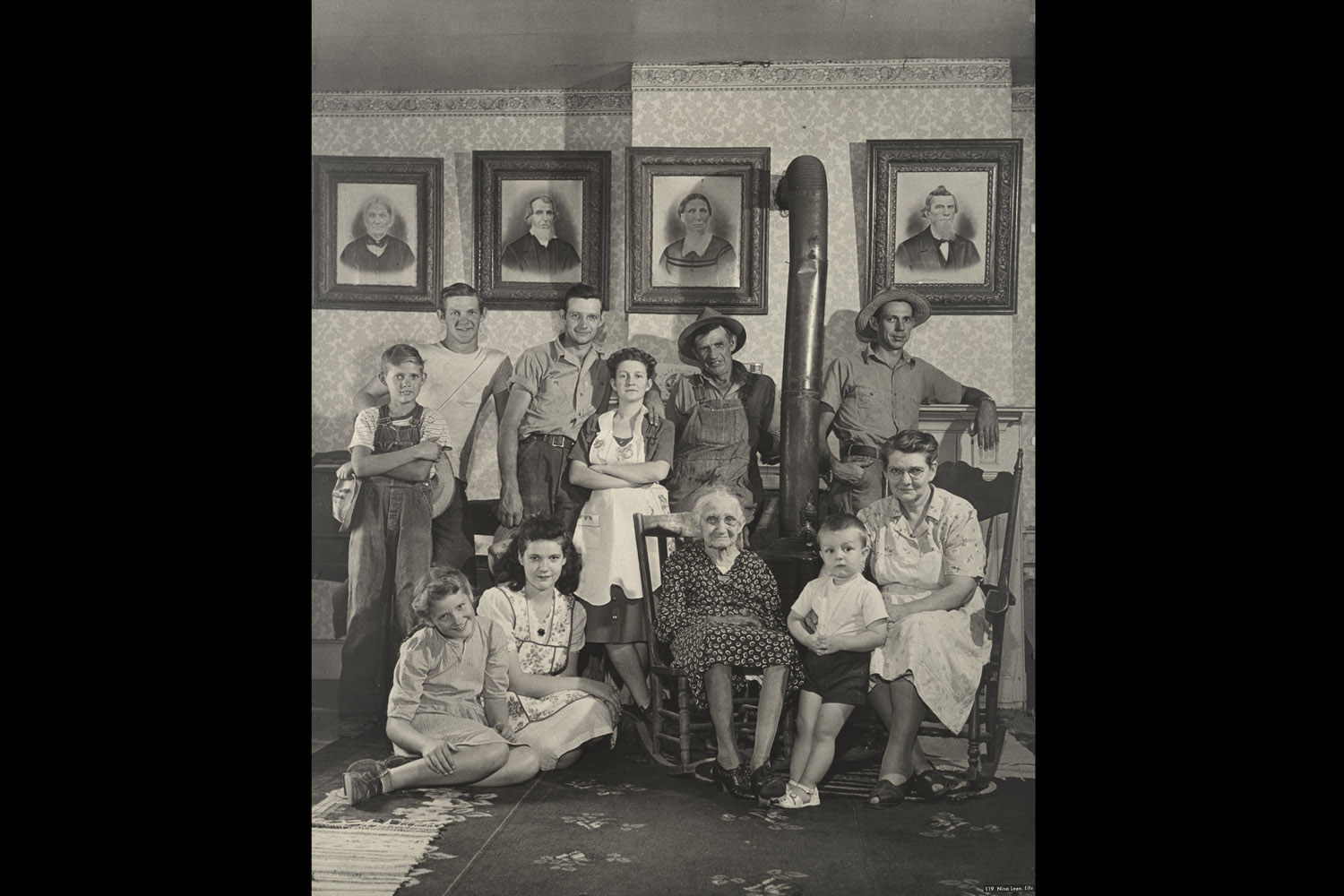 Four generations of farmers in this Ozark family posing in front of a wall with portraits of their fifth generation, 1946.