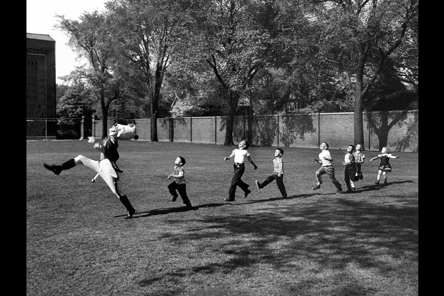 Uniformed drum major for the University of Michigan marching band practicing his high-kicking prance as he leads a line of seven admiring children who are all trying to imitate his flamboyant technique while marching across the campus lawn, 1951.