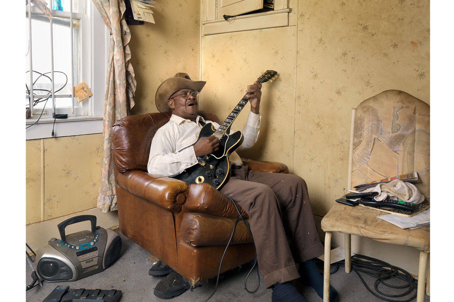 Glemie Playing the Blues, Westside, Detroit, 2011                                                              Glemie, a retired truck driver and fifty-year resident of Detroit, is an accomplished blues singer, but he's also known for his small game hunting skills.  Every fall he hunts an average of 150 raccoons, which he skins, dresses, and sells as food to clients.  This extra income supplements his meager retirement benefits.