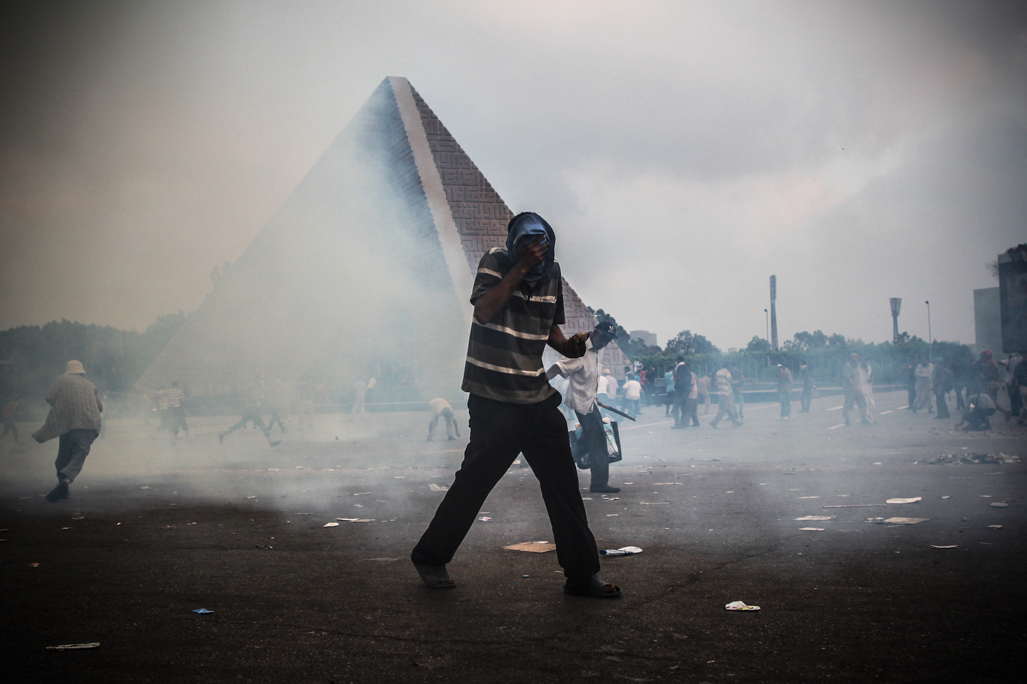 A Morsi supporter covers his face from the tear gas shot by police during the clashes. In the background is the unknown soldier memorial where President Sadat is buried.