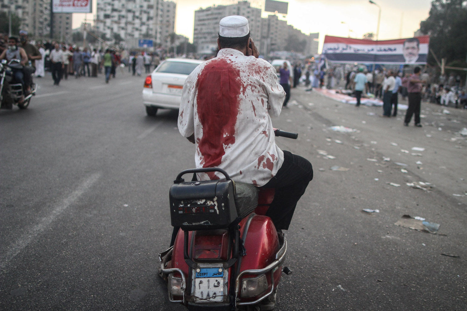 A man with a blood-stained shirt pauses at the scene.