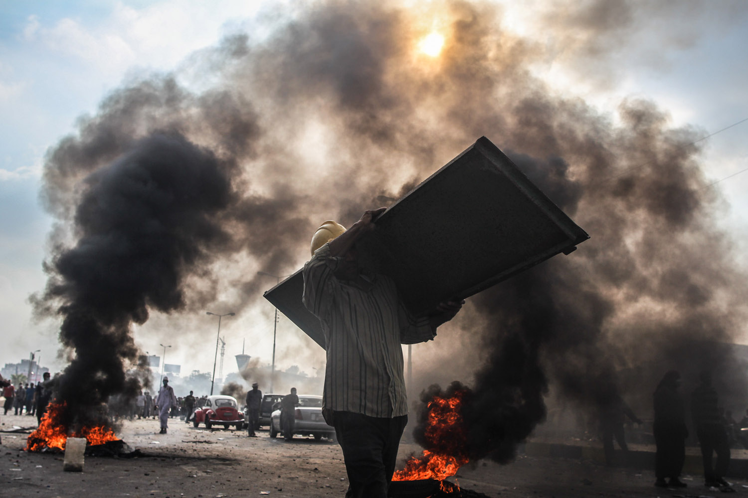 A Morsi supporter carries a steel door to help bolster defenses at the frontlines.