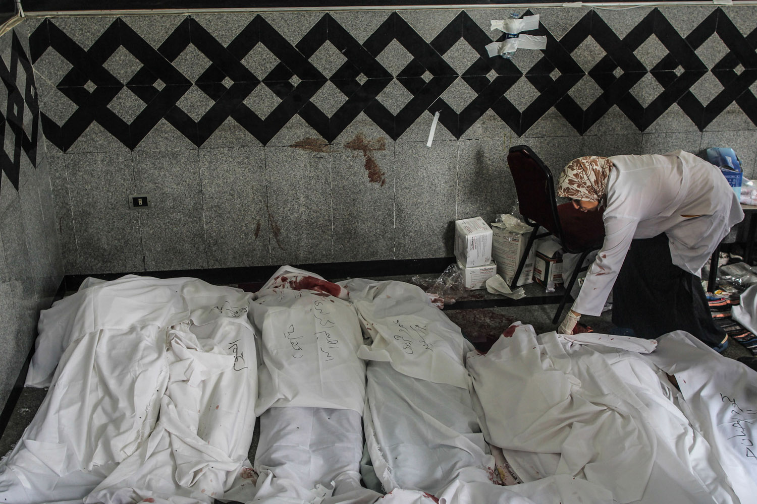 A doctor tries to identify the body of a Morsi supporter killed during the clashes.