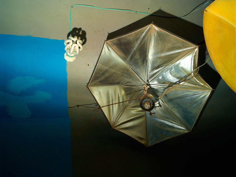 Inside Malick Sidibe's Bamako studio, a strobe lighting system has been updated to accomidate his son Kareem's job as an I.D. photographer.