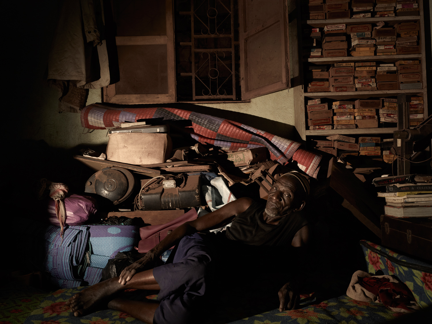 Samba Sidibe (Malick's younger brother) sits on the floor surrounded by old studio equipment and film negatives in Malick's bedroom.
