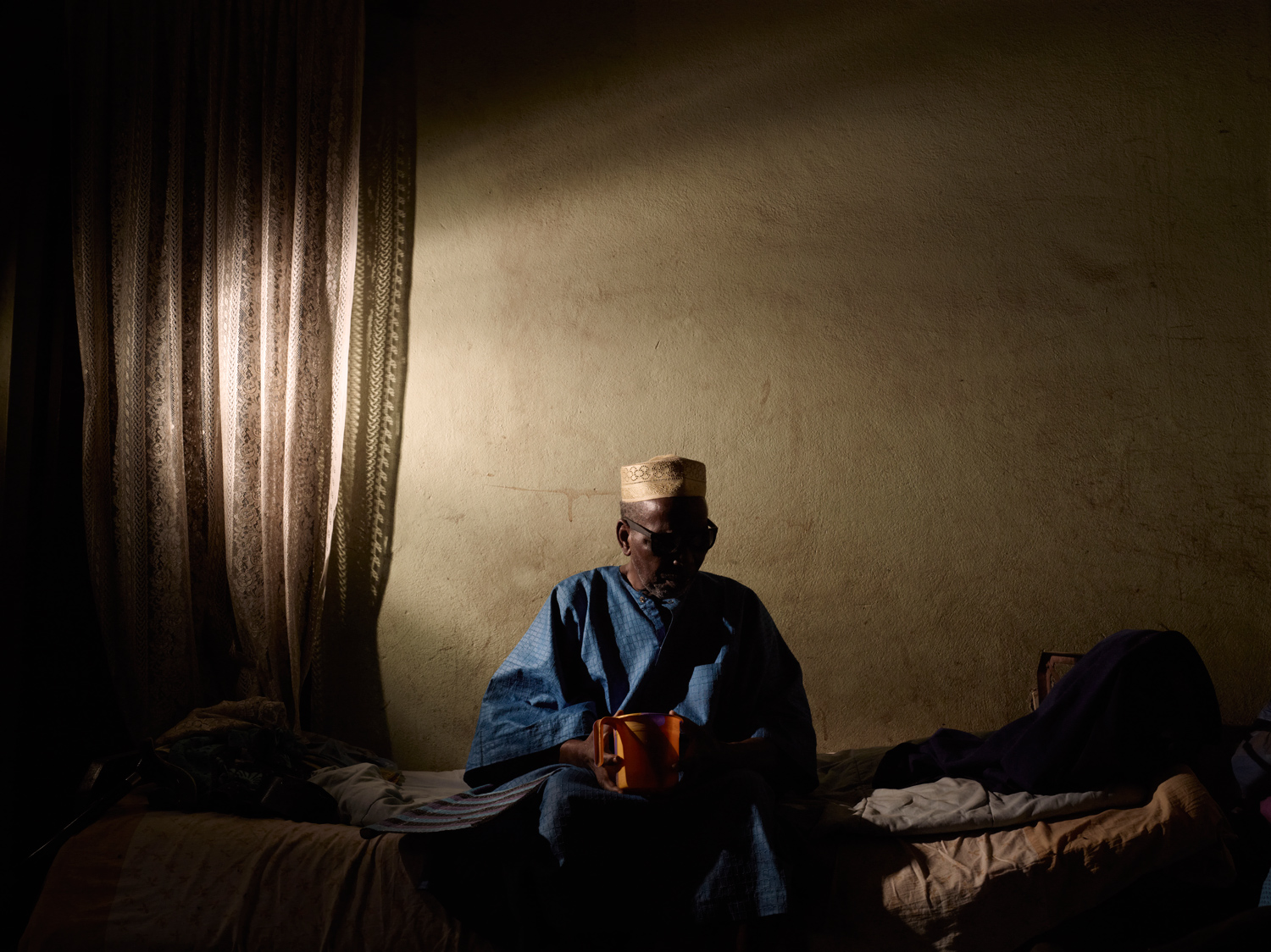 Malick Sidibe sits in his bed in his Bamako home. With temperatures rising to 110 degrees Fahrenheit, the heat take its toll on the aging Sidibe. His younger brother Samba and his sons help keep him cool using a hand fan.