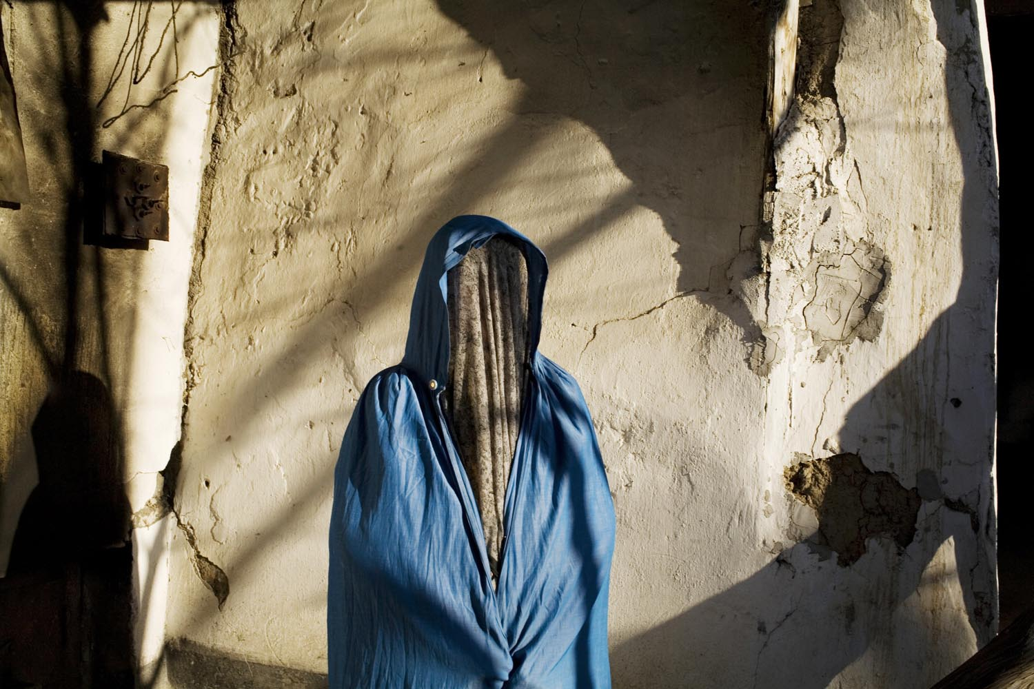An Uzbek woman poses in the courtyard of her home in the outfit her husband told her to wear in public. Banned in Soviet times, the paranja is the traditional robe worn by women in the Fergana Valley.                               Karasu, Kyrgyzstan
