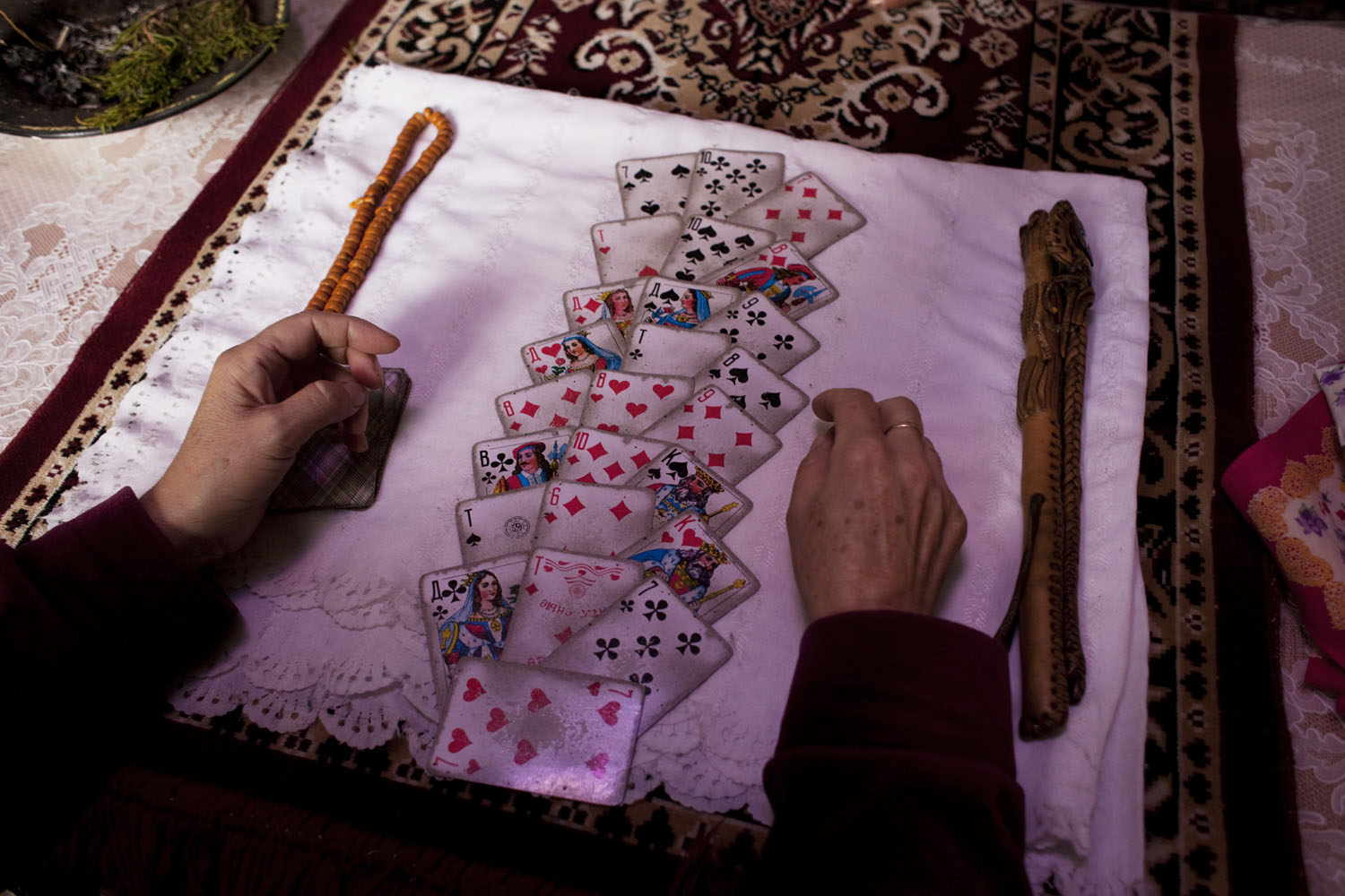 The shaman Burul lays out playing cards on her kitchen table to study her client's life.                               Talas, Kyrgyzstan