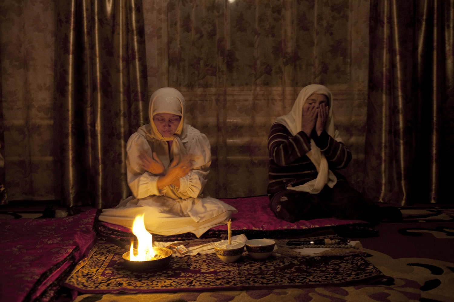 Late at night, a shaman called Burul performs Zhar Solu to purify the home and soul of her friend. They light candles to call the spirits.                               Talas, Kyrgyzstan