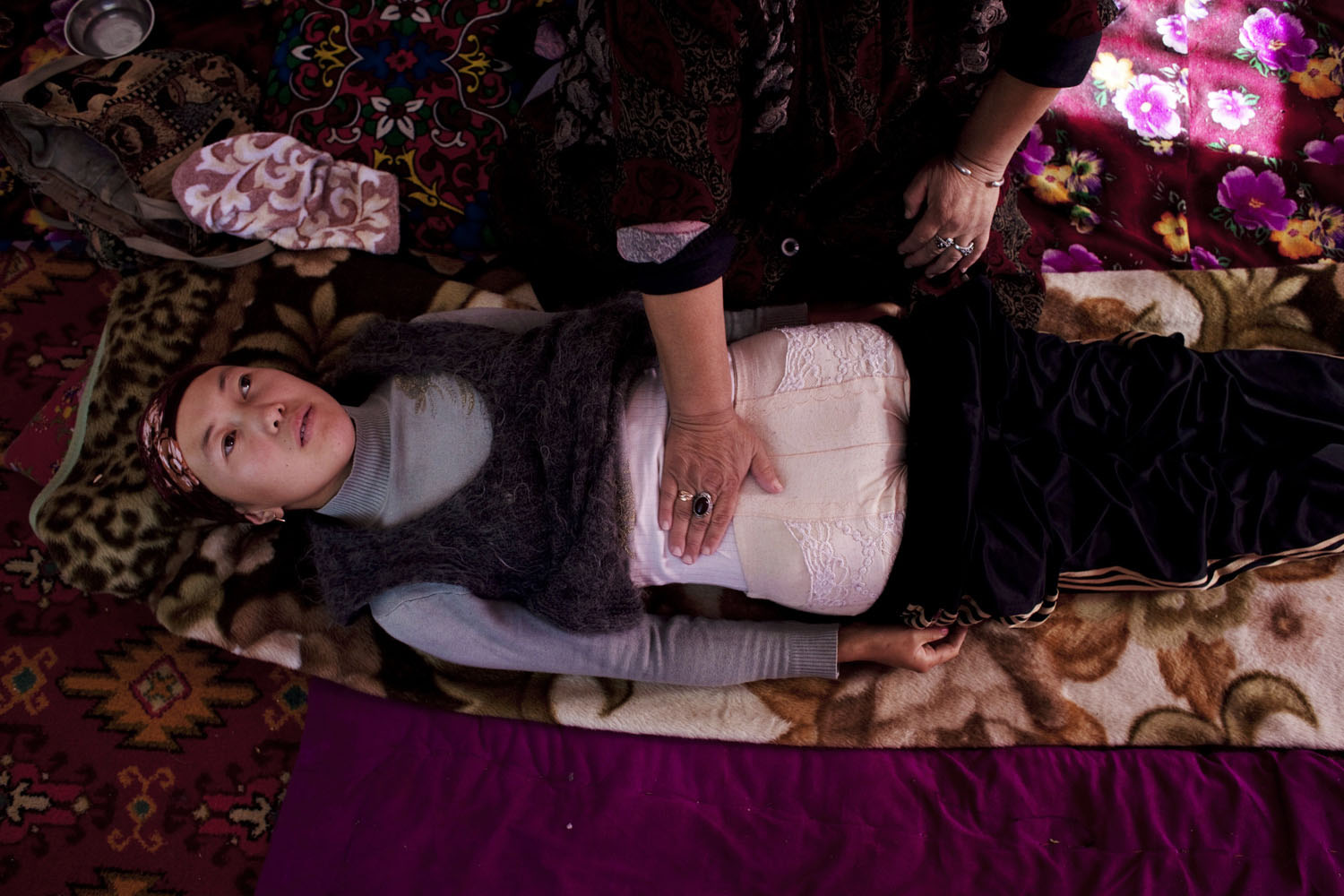 A shaman named Bubusade treats a young woman from her village with a massage.                               a village near Talas, Kyrgyzstan
