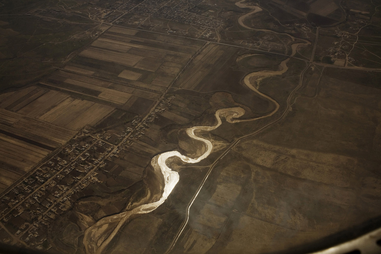 The Syr Darya, an irrigation canal, and cotton fields seen through an airplane window in spring.                               Tashkent, Uzbekistan