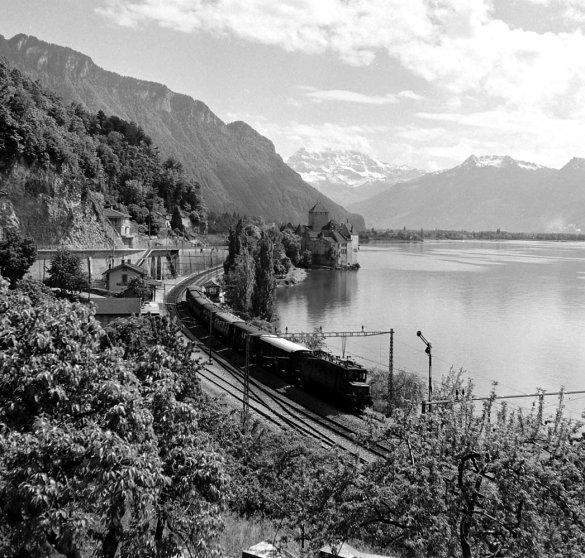 The Simplon-Orient Express alongside Lake Geneva, near historic Chillon Castle.