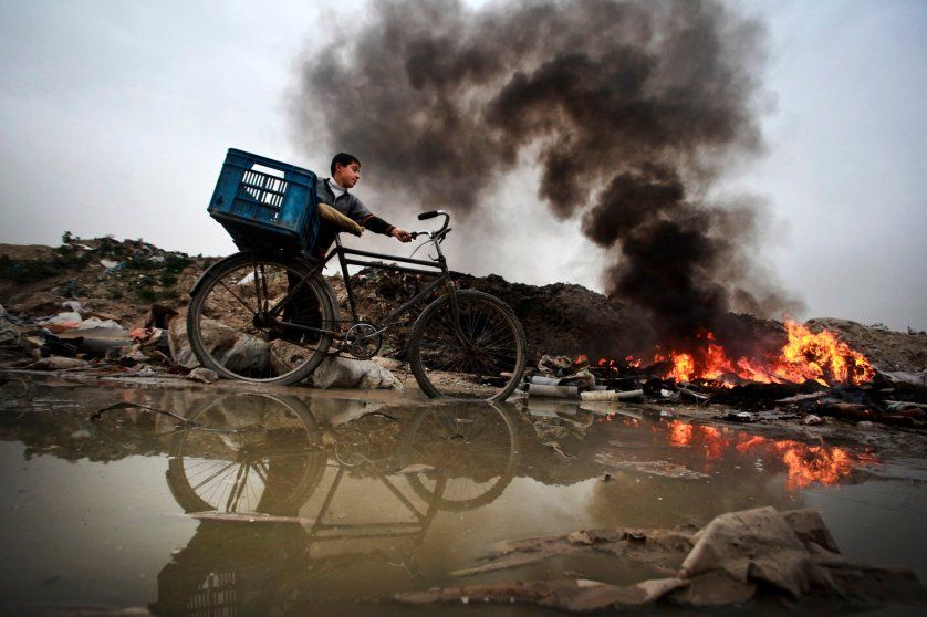 A Palestinian child drives his bicycle along a waste dump in central Gaza Strip