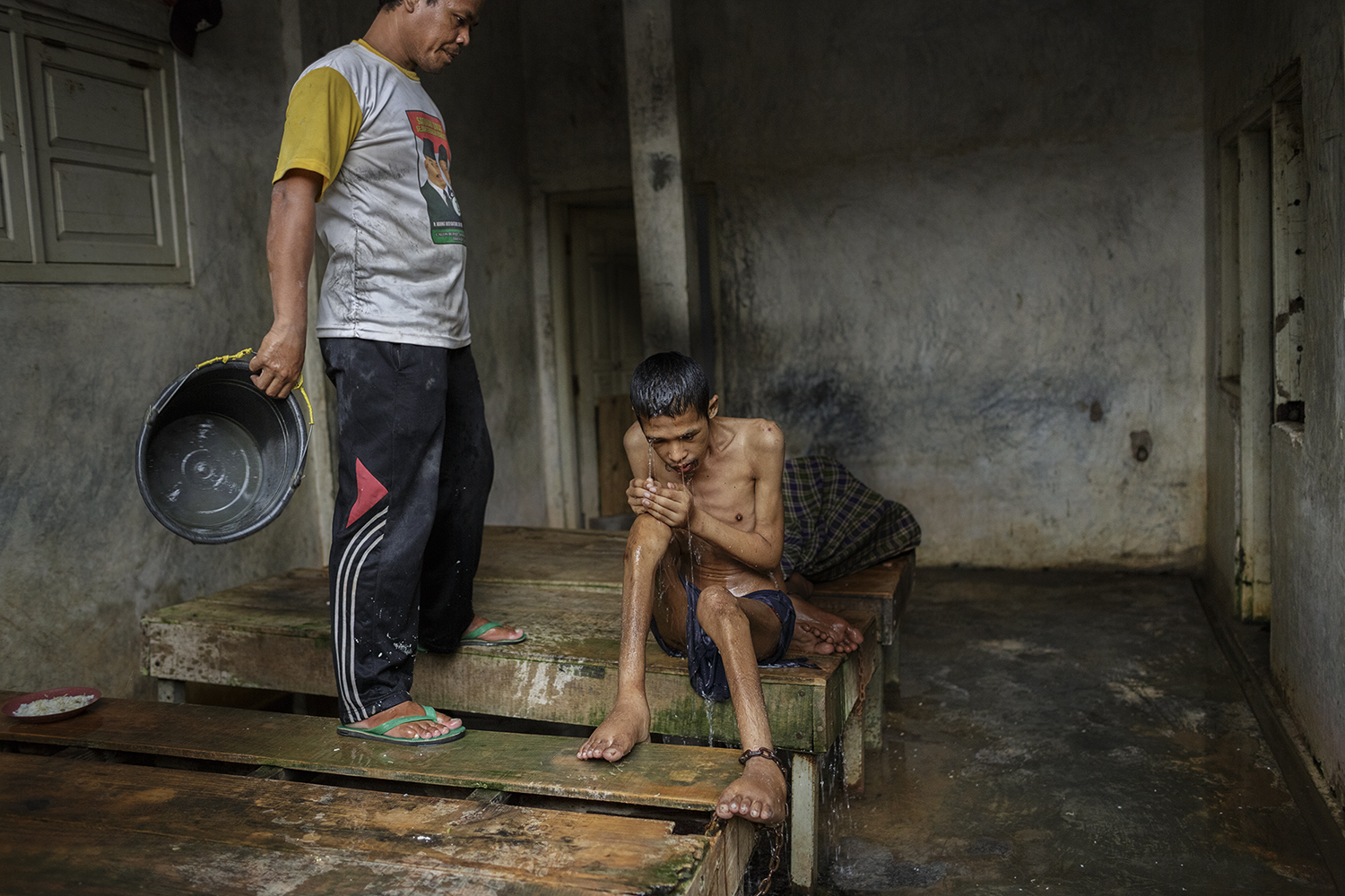 Mustofa, the sole assistant and primary caregiver at Kyai Syamsul's family-run shelter, gives a shower to Akrom, 25 years old.