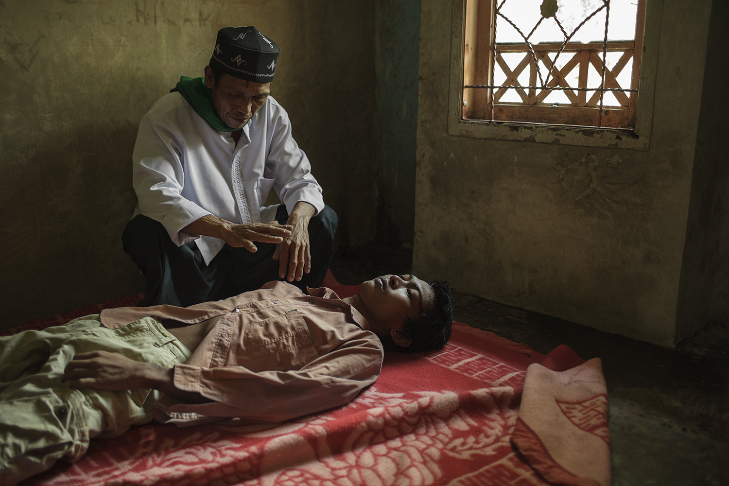 Didin, 25 years old, receives treatment from Abah Sanuk, a traditional healer using Silat, a martial arts method. Shamans and traditional healers are the most popular and more affordable mental health care providers throughout Indonesia.