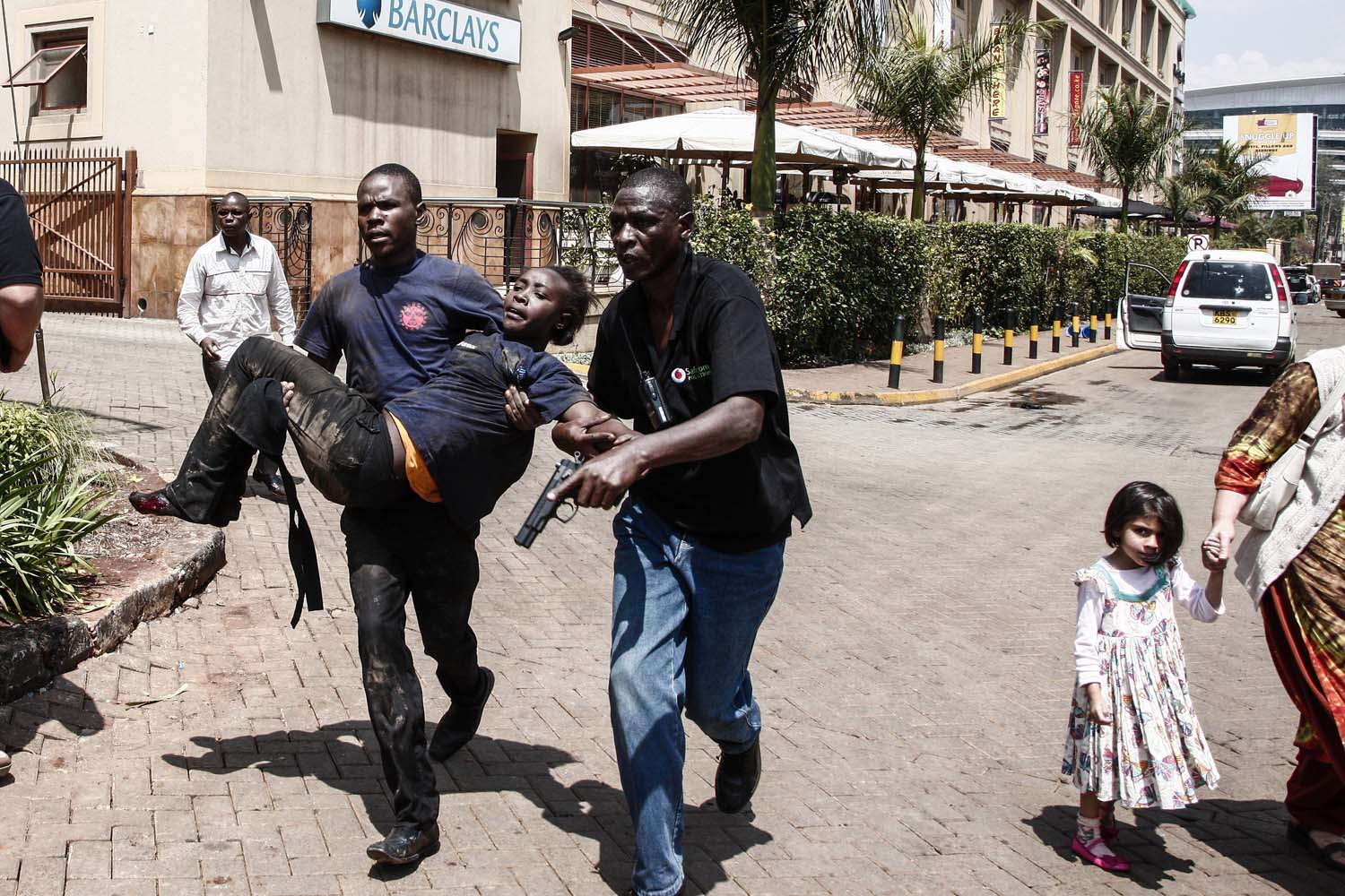 Sept. 21, 2013. Rescuers carry an injured woman away from the Westgate Shopping Center after a shootout in Nairobi, Kenya.