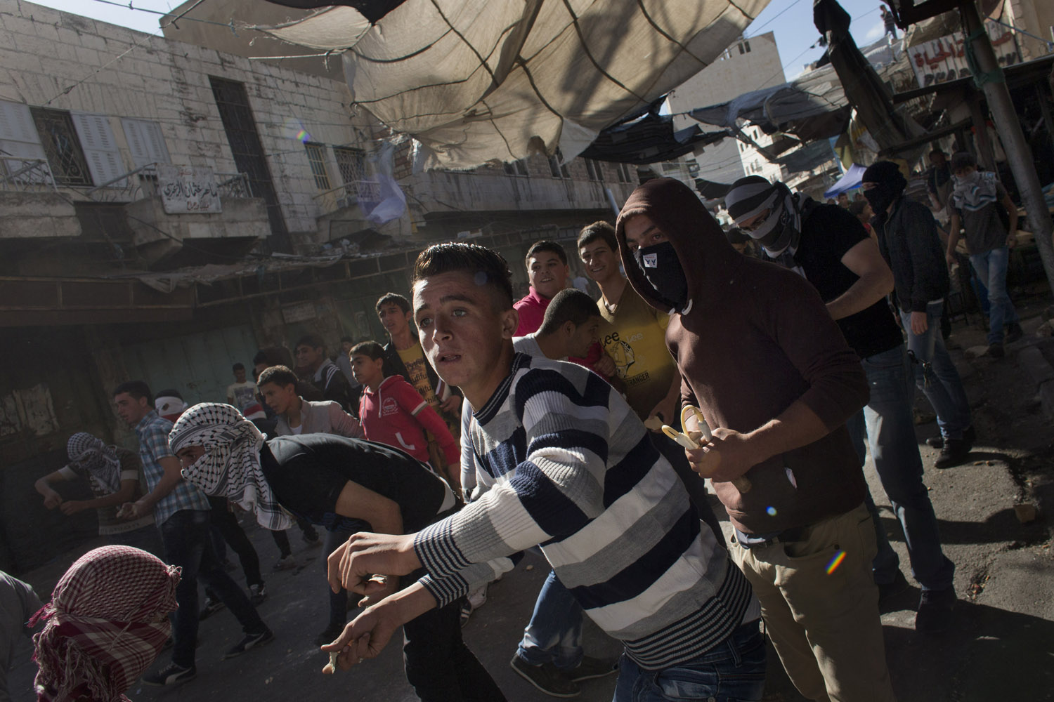 Sept. 23, 2013. Palestinians throw stones toward Israeli soldiers, not pictured, in the West Bank city of Hebron.