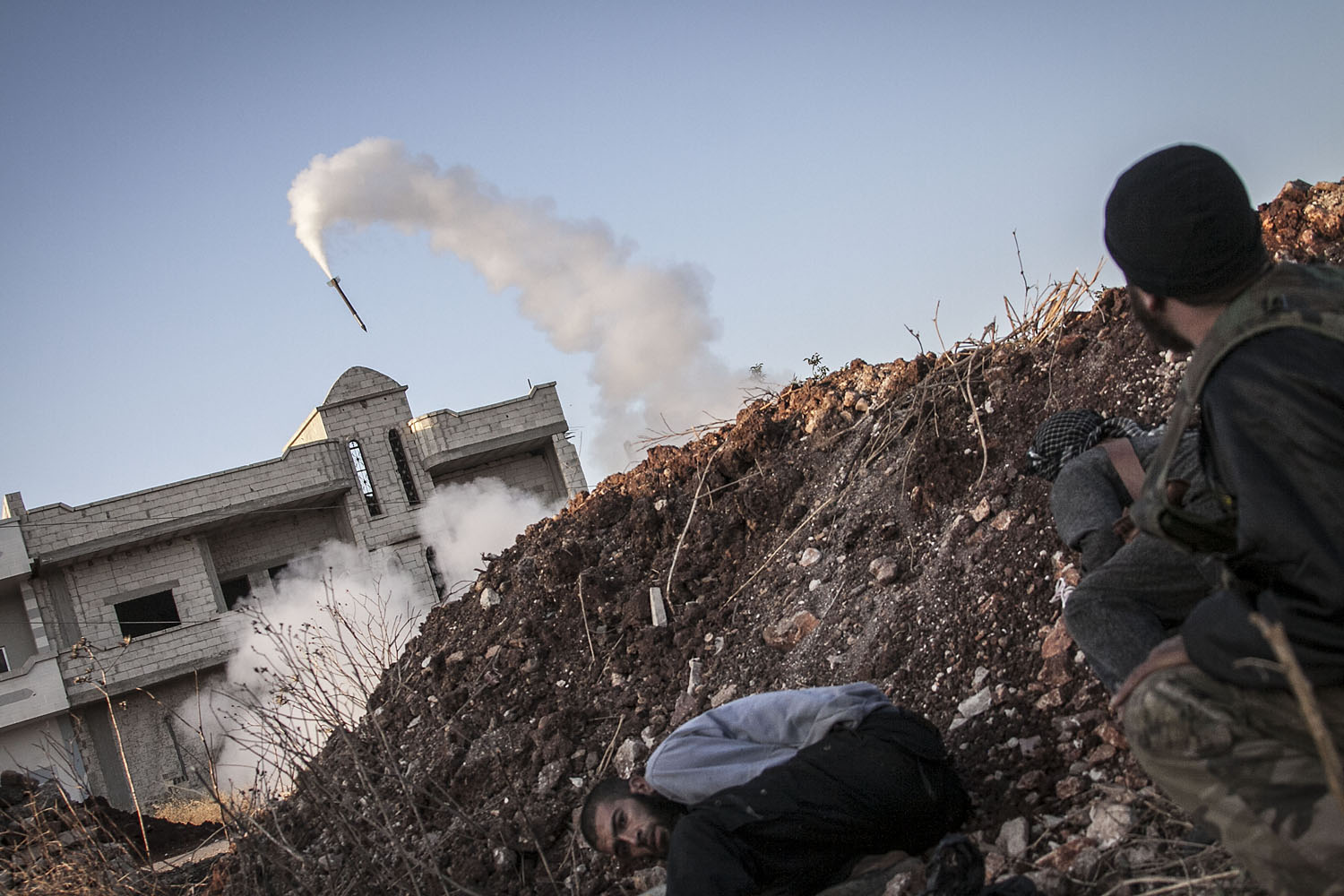 Sept. 20, 2013. Free Syrian Army fighters take cover moments after shelling a rocket on government forces in Kafr Nboudah village, Idlib province, northern Syria.