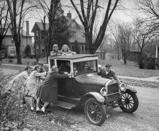 Gang of teen-agers push boyfriend's model T to get it started. Car is 17 years old and can hold 12 boys and girls. Favorite ride is out to football game.