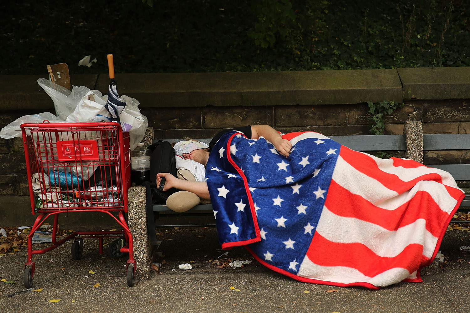 A homeless man sleeps under an American Flag blanket on a park bench in the Brooklyn borough of New York City on Sept. 10, 2013.