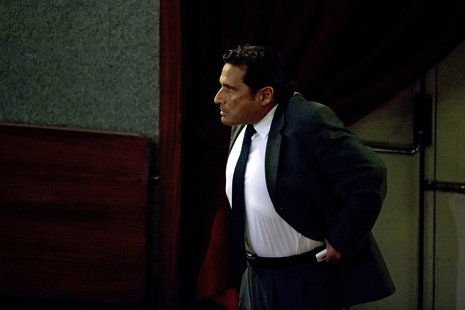 Sept. 23, 2013. Captain Francesco Schettino adjusts his trousers as he walks in the court room of the converted Teatro Moderno theater for his trial, in Grosseto, Italy.