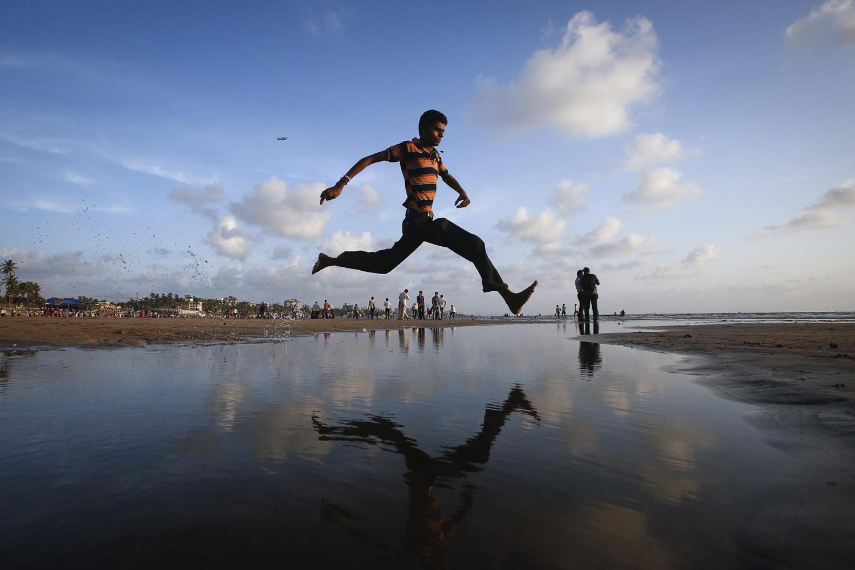 Sept. 2, 2013. A man jumps over a water stream on a beach along the Arabian Sea in Mumbai.