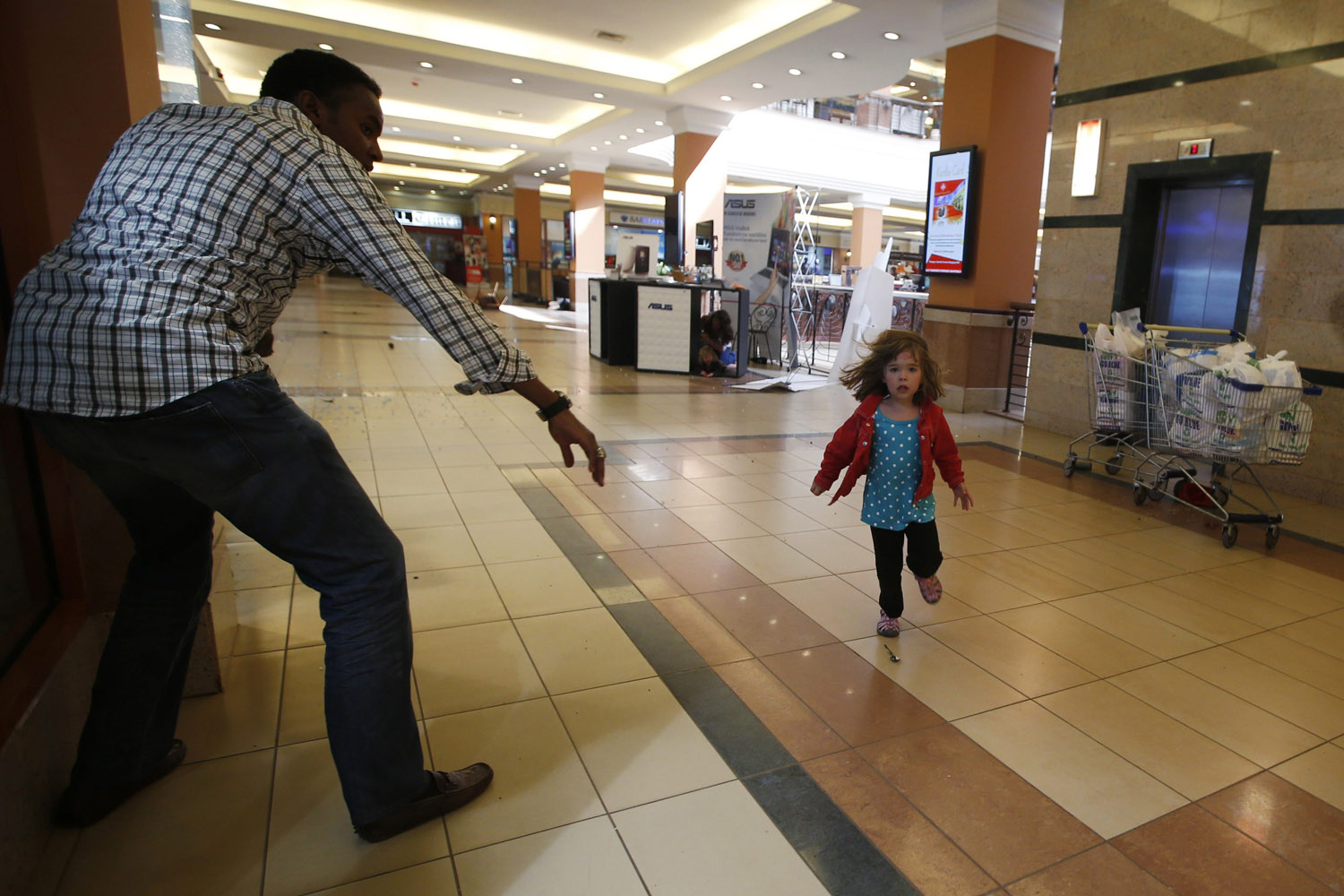 Sept. 21, 2013. A child runs to safety as armed police hunt gunmen who went on a shooting spree at Westgate Shopping Center in Nairobi, Kenya.