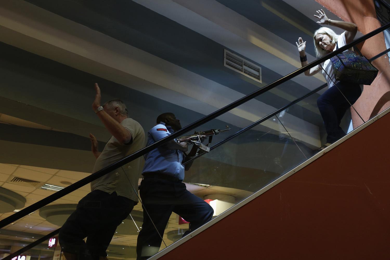 Sept. 21, 2013. A police officer (C) secures an area as civilians flee inside Westgate Shopping Center in Nairobi, Kenya.
