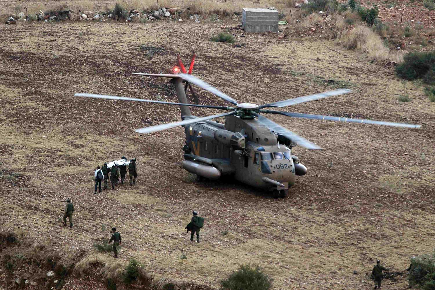 Sept. 21, 2013. Israeli soldiers carry the body of a fellow soldier who was killed near the West Bank town of Qalqilya onto a military helicopter.