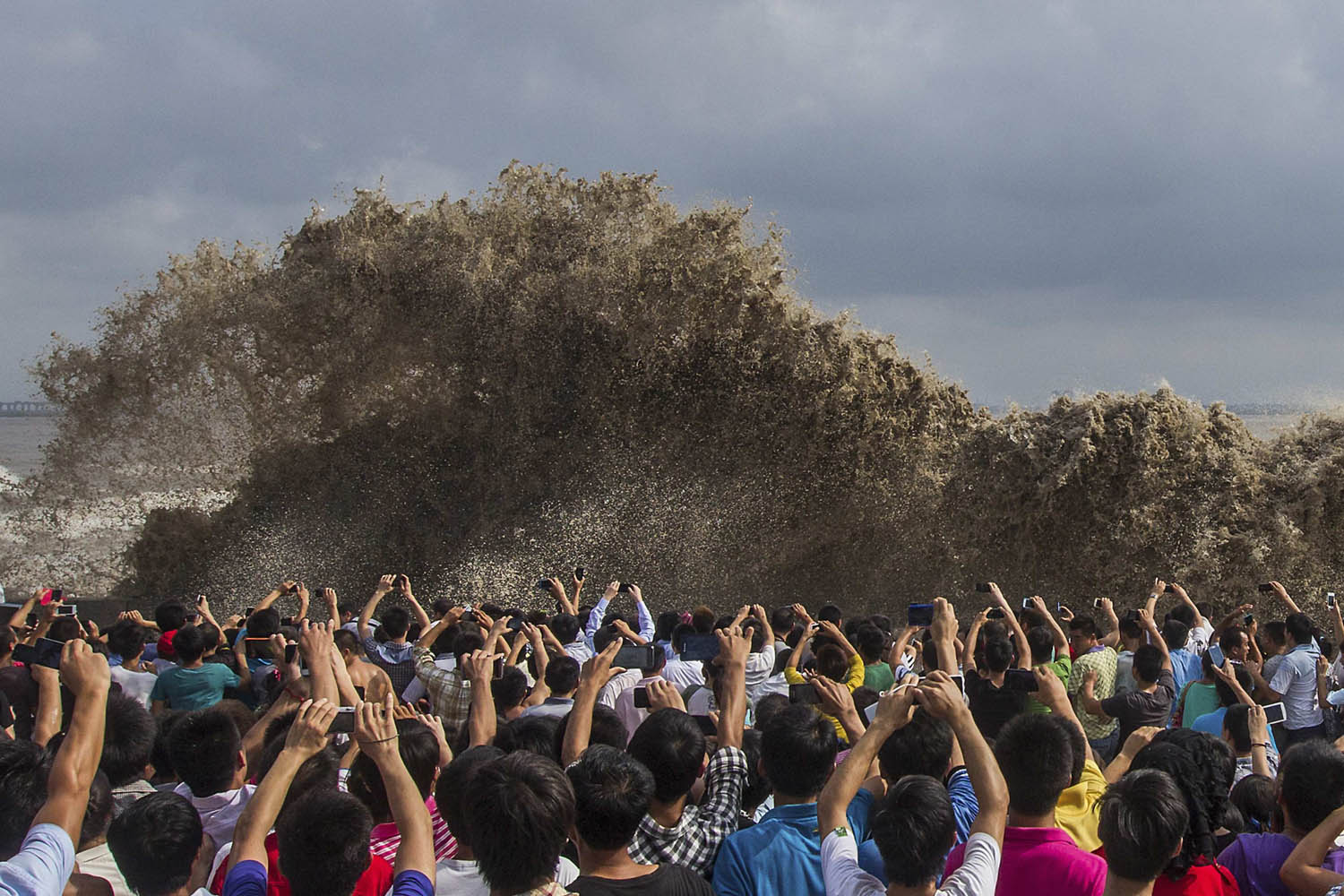 Sept. 22, 2013. Visitors take pictures of tidal waves under the influence of Typhoon Usagi in Hangzhou, Zhejiang province, China.